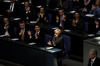 23 MAR 2012, BERLIN/GERMANY:<br /> Angela Merkel, CDU, Bundeskanzlerin, sitzt in einem Sonnenstrahl, reflektiert aus der Kuppel des Bundestages, und applaudiert während der Rede von Joachim Gauck (unten rechts), Personen in der Regierungsbank: Peter Ramsauer, CSU, Bundesverekehrsminister, Daniel Bahr, FDP. Bundesgesundheitsminister, Kristina Schroeder, CDU, Bundesfamilienministerin, Thomas de Maiziere, CDU, Bundesverteidigungsminister (obere Reihe, v.L.n.R.), Peter Friedrich, CSU, Bundesinnenminister, Michael Georg Link, FDP. Staatsminister im Auswaertigen Amt, Philipp Roesler, FDP, Bundeswirtschaftsminister, Angela Merkel, CDU, Bundeskanzlerin (untere Reihe, v.L.n.R.), gemeinsame Sitzung von Bundestag und Bundesrat anl. der Vereidigung des Bundespraesidenten, Plenum, Deutscher Bundestag<br /> IMAGE: 20120323-02-033<br /> KEYWORDS: Sonne, Applaus, applaudiern, Regierungsbank, Kristina Schröder, Thomas de Maizieré, Philipp Rösler
