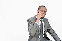 African American businessman conversing on cell phone over white background