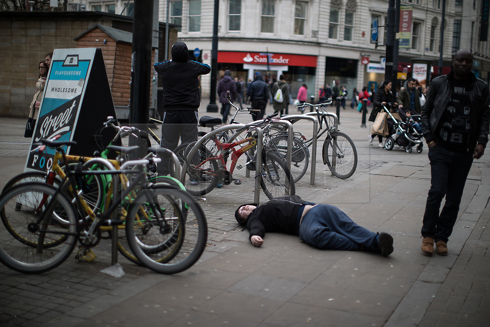© Licensed to London News Pictures . 06/04/2017 . Manchester , UK . A man lies flat out on the pavement on Piccadilly Gardens . An epidemic of abuse of the drug spice by some of Manchester's homeless population , in plain sight , is causing users to experience psychosis and a zombie-like state and is daily being witnessed in the Piccadilly Gardens area of Manchester , drawing large resource from paramedic services in the city centre . Photo credit : Joel Goodman/LNP