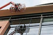 Schilders staan in een hoogwerker om de dakrand te verven.<br /> <br /> Painters are standing on a platform.
