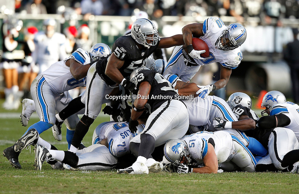Detroit Lions running back Kevin Smith (30) gets stuffed in the air by Oakland Raiders outside linebacker Aaron Curry (51) and Raiders teammates as Smith tries to leap over the pile on third down and one to go during the NFL week 15 football game against the Oakland Raiders on Sunday, December 18, 2011 in Oakland, California. The Lions won the game 28-27. ©Paul Anthony Spinelli