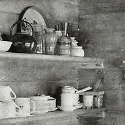 A still life image of items on kitchen shelves. This image was created using the Bromoil process.