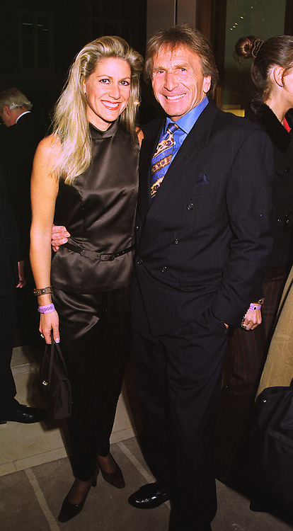 Racing driver DEREK BELL and his fiance MISS MISTI SPRINKLE, at a party in London on 24th February 1998.MFP 89