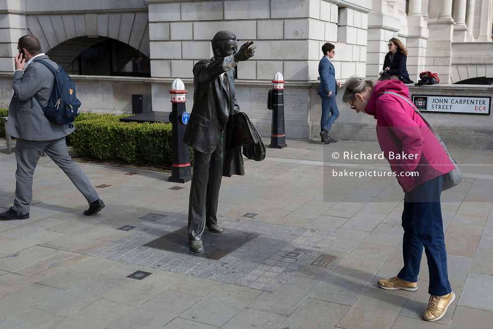 A passer-by studies the details of artist John Seward Johnson's sculpture, entitled 'Taxi!' (1983) on John Carpenter Street in the City of London, the capital's financial district, on 25th March 2019, in London, England.