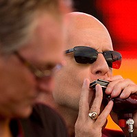"Bruce Willis performs on the harmonica with his band ""The Bruce Willis Blues Band"" during the Netflix Live On Location concert and movie series in the Rocket Garden at the Kennedy Space Center Visitors Complex in Cape Canaveral, Florida August 2, 2007. REUTERS/Scott Audette (UNITED STATES)"