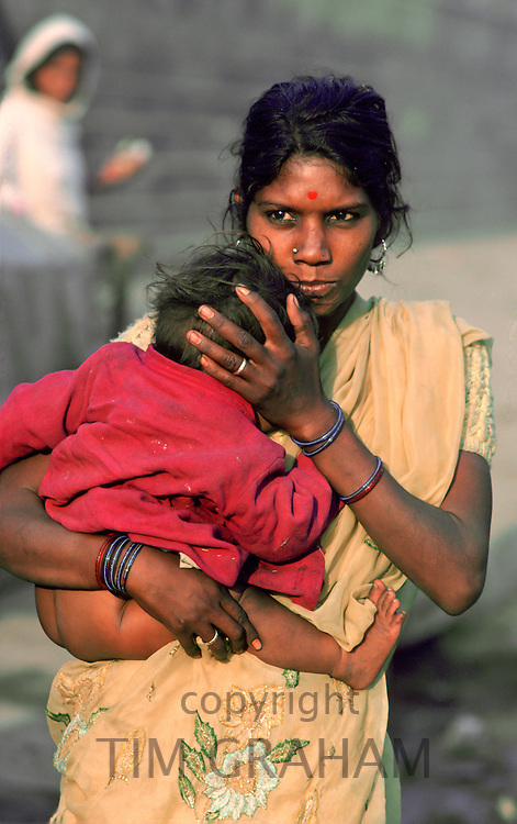 Mother holding her young baby as she walks through the streets of Delhi, India