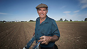 I drove past Gary Burton as he wheeled a strange device across a brown dirt paddock. It was like a wheelbarrow without the barrow. I had to stop and ask for a photograph.<br /> <br /> While I went about setting up my paraphernalia we talked about his farm, his grandfather, his father and his children. He told me about the watermelon plants that were just sprouting and about the ancient machine he was using to tend them.<br /> <br /> I made pictures as I listened. This is the moment I felt I best appreciated the stories his words, face and well worked hands were telling me.