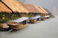 Long tail boats wait out the rain at the Kwai River Jungle Rafts in Kanchanaburi Province, Thailand