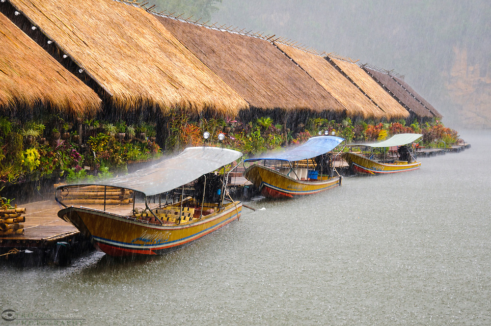 Long tail boats wait out the rain at the Kwai River Jungle Rafts in Kanchanaburi Province, Thailand