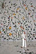 Man standing in front of interior wall covered with floral inlaid marble at the Sheikh Zayed Grand Mosque in Abu Dhabi, UAE.