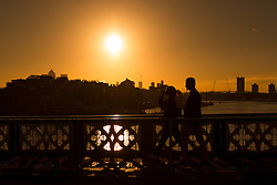 © Licensed to London News Pictures. 23/09/2016. LONDON, UK.  People cross Tower Bridge as the sun rises behind on the River Thames in London during clear and sunny weather this morning. Today is the second day of British autumn.  Photo credit: Vickie Flores/LNP
