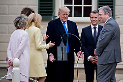 U.S. President Donald Trump, center, speaks as Doug Bradburn, president and chief executive officer of George Washington's Mount Vernon, from right, Emmanuel Macron, France's president, Brigitte Macron, France's first lady, U.S. First Lady Melania Trump and Sarah Miller Coulson, regent with the Mount Vernon Ladies' Association, listen while touring outside the Mansion at the Mount Vernon estate of first U.S. President George Washington in Mount Vernon, Virginia, U.S., on Monday, April 23, 2018. As Macron arrives for the first state visit of Trump's presidency, the U.S. leader is threatening to upend the global trading system with tariffs on China, maybe Europe too. Photographer: Andrew Harrer/Bloomberg