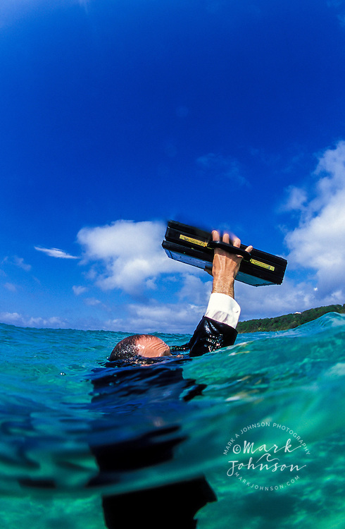 Australia, Queensland, businessman in sea trying to save briefcase.  MR available.