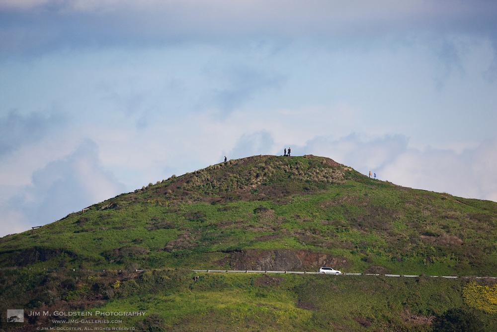 Tourists atop a green Twin Peaks mountain top - San Francisco, California