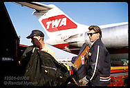 Workers load baggage from arriving TWA jet into luggage cart at Lambert Intl Airport; St. Louis. Missouri