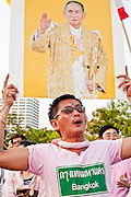 "Apr. 2, 2010 - BANGKOK, THAILAND: A supporter of the Thai monarchy holds up a photo of the King during a Pink Shirt protest in Bangkok Friday. Thousands of ""Pink Shirts,"" who claim to be neither ""Red Shirts"" nor ""Yellow Shirts"" nicknames for Thailand's dueling political forces, gathered in Lumpini Park in central Bangkok Friday evening to call for ""peace in the land,"" a play on the Red Shirts slogan, ""Red in the Land."" The ""Pink Shirts"" represented educators, business people and people in the tourist industry, all of which have been hurt by the ongoing political protests that have disrupted life in the Thai capital. The ""Pink Shirts"" stressed their loyalty to His Majesty Bhumibol Adulyadej, the King of Thailand, and chanted for the Red Shirts to ""Get Out!"" of Bangkok.    PHOTO BY JACK KURTZ"