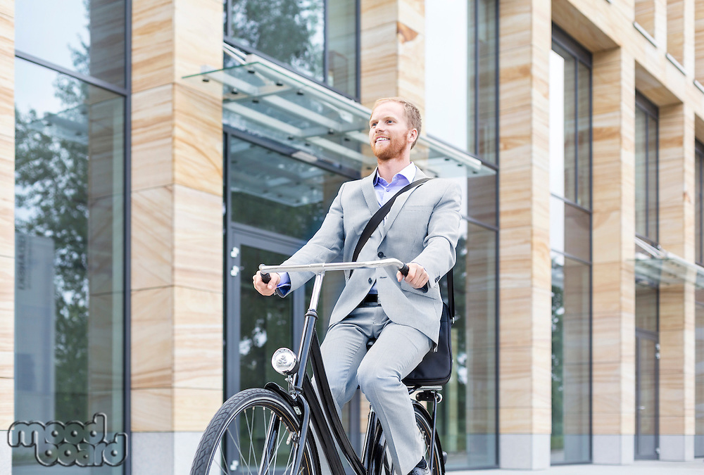 Smiling businessman riding bicycle outside building