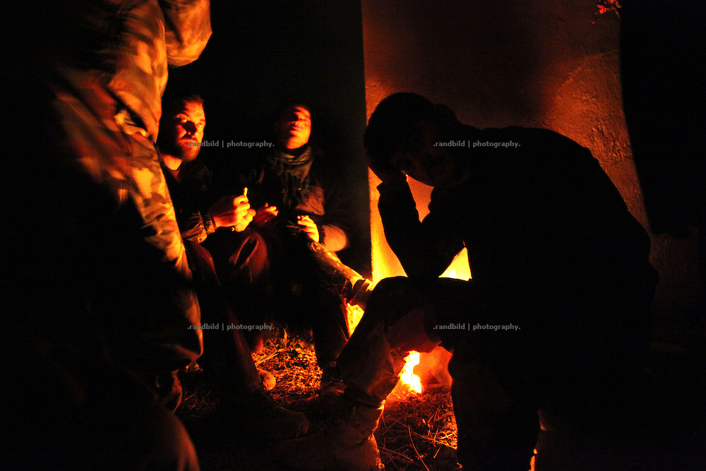 Soldiers of the Free Syrian Army resting at a campfire during their exhausting walk across the mountainous border from Turkey to Syria, Al Janoudiyah, Syria.