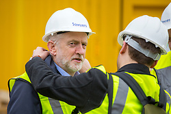 © Licensed to London News Pictures. 15/03/2018. Carlisle UK. Labour Leader Jeremy Corbyn is helped by an aid to put a high viz jacket on during a visit to a building site in Carlisle, Cumbria today. Photo credit: Andrew McCaren/LNP