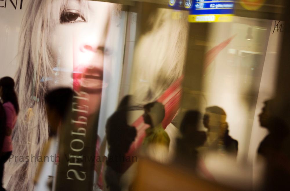 Shoppers walk past advertisements inside the Inorbit Mall Malad, in Mumbai, on Sunday Dec. 28, 2008.  Photographer:Prashanth Vishwanathan
