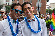 Two men waering bow ties and blue leis march on Christopher Street.