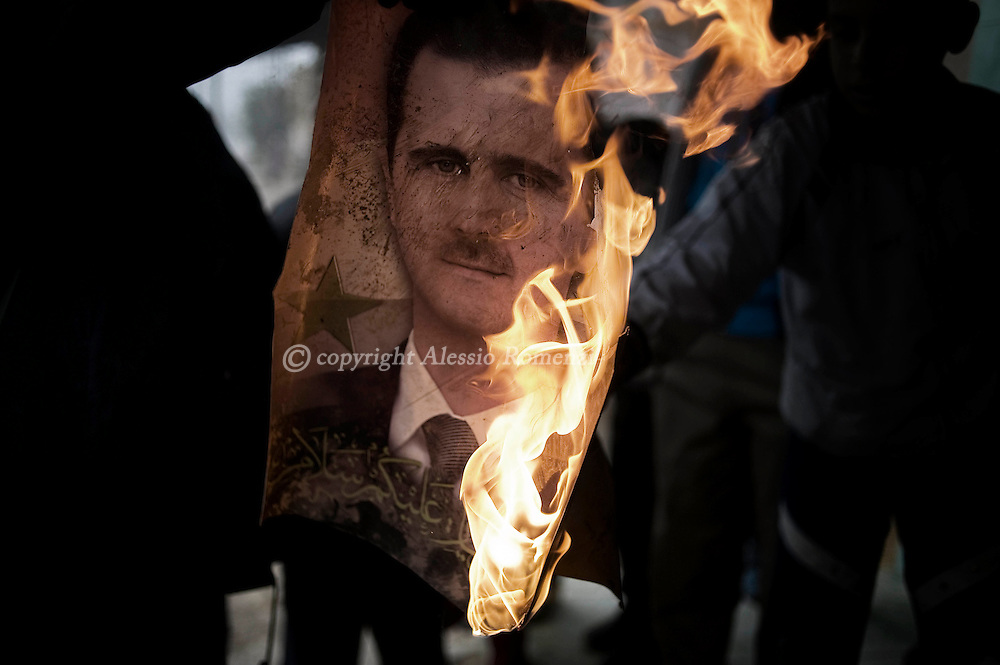 SYRIA - Al Qsair. A member of Free Syrian Army burns a portrait of Bashar Al Assad in Al Qsair, on January 25, 2012. Al Qsair is a small town of 40000 inhabitants, located 25Km south-west of Homs. The town is besieged since the beginning of November and so far it counts 65 dead. ALESSIO ROMENZI