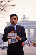March 13, 1990. Berlin, Federal Republic of Germany. In front of Brandenburg Gate, a Japanese TV journalist explains the replacement of the East Mark (above) by the Deutsche Mark (DM, German Mark). (Photo Heimo Aga)