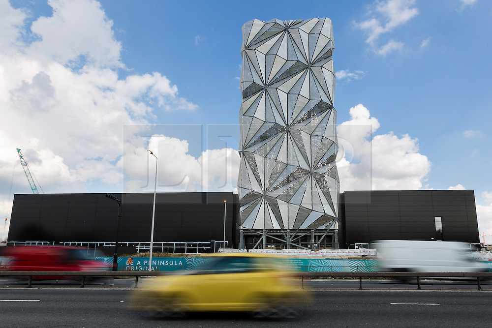© Licensed to London News Pictures. 21/09/2016. LONDON, UK.  The Optic Cloak sculpture is seen as cars travel on the approach to the Blackwall Tunnel near the Greenwich Peninsula.  The Optic Cloak, designed by artist, Conrad Shawcross is based on tetrahedra and is the exterior camouflage for a 49 meter tall chimney, that will house a new low-carbon energy centre and provide power to new homes in the area.  Photo credit: Vickie Flores/LNP