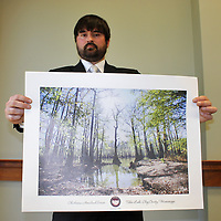 Bret Holt of the Chickasaw Inkana Foundation in Tupelo holds a print of Tibbee Lake in Clay County, an important historical site in Chickasaw history. Holt was the guest speaker for the April 13 Amory Rotary Club meeting.
