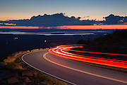 A car streaks down Cadillac Mountain at sunset as a thunderstorm casts rain below clouds in the distance.