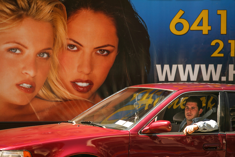 A man waits on a red light with a  sex line advert on the background.
