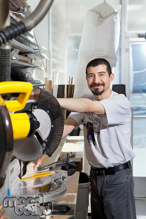 Portrait of a Hispanic employee using circular saw