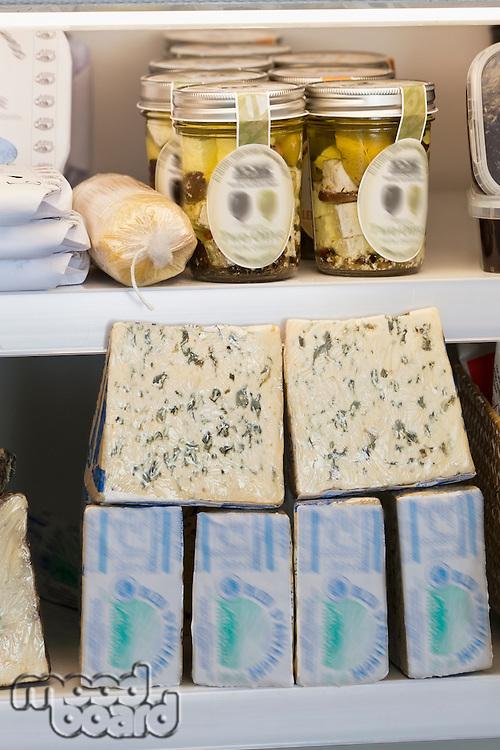 Variety of cheese blocks and jars on shelf