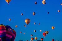 Hot air balloons flying over Balloon Fiesta Park during the Albuquerque International Balloon Fiesta, Albuquerque, New Mexico USA.