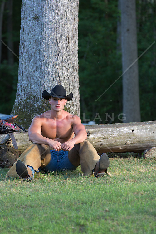 shirtless cowboy sitting in the woods