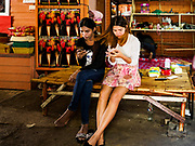 20 MARCH 2017 - BANGKOK, THAILAND: Girls use their smart phones in what used to be a fireworks shop in an alley in Pom Mahakan. The fireworks shop was evicted in early March. The final evictions of the remaining families in Pom Mahakan, a slum community in a 19th century fort in Bangkok, have started. City officials are moving the residents out of the fort. NGOs and historic preservation organizations protested the city's action but city officials did not relent and started evicting the remaining families in early March.               PHOTO BY JACK KURTZ