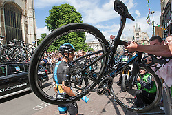 Image ©Licensed to i-Images Picture Agency. 07/07/2014. Cambridge, United Kingdom. Tour de France Stage 3 Cambridge. Richie Porte has a mechanical problem at Kings College. A spectators tries to remove his bike from the road. Picture by Terry Harris / i-Images