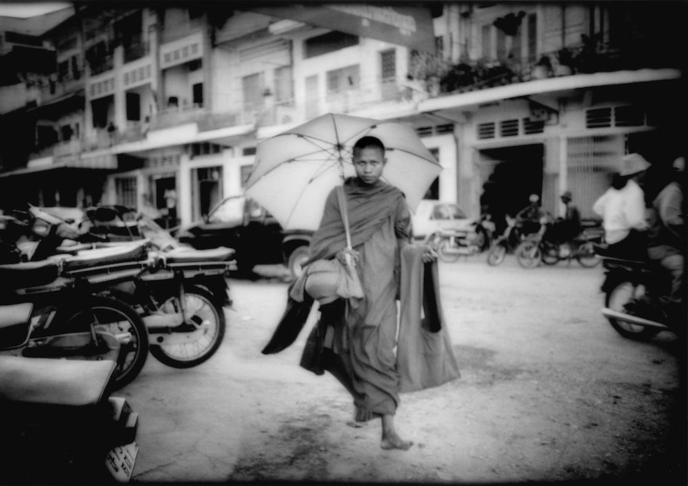Bonze making morning rounds for alms, Phnom Penh, Cambodia.