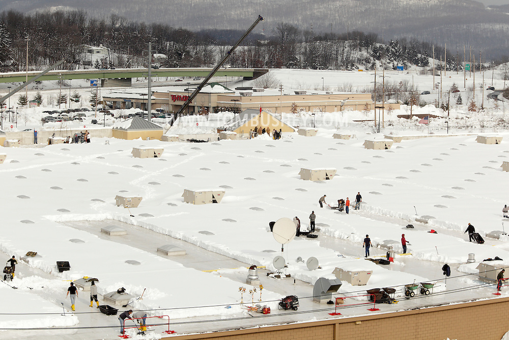 Harriman, New York - Workers in the foreground use shovels to remove snow from the roof of the Walmart store after a two-day storm dropped more than 30 inches of snow on Feb. 27, 2010. Cranes in the background are lifting tarps full of snow off the roof.