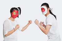 Portrait of young man and woman with Asian flags painted on face holding up their fists to fight against white background