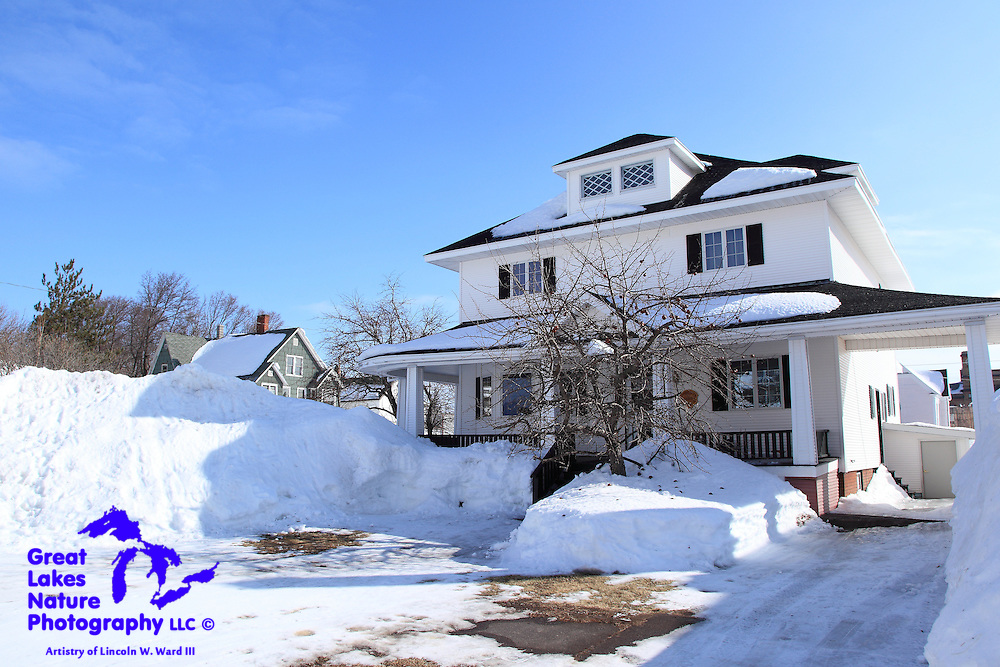 """One of the many beautiful Calumet/Laurium homes, nestled in a deep blanket of snow. With street parking being out of the question in Calumet during the winter, people create """"parking nooks"""" wherever they can."""