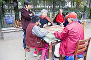 CHINA, BEIJING: Elderly Chinese women and one man playing mahjong, a traditional Chinese game of skill and luck using tiles, in a neighborhood park in Beijing as spectators gather to watch.