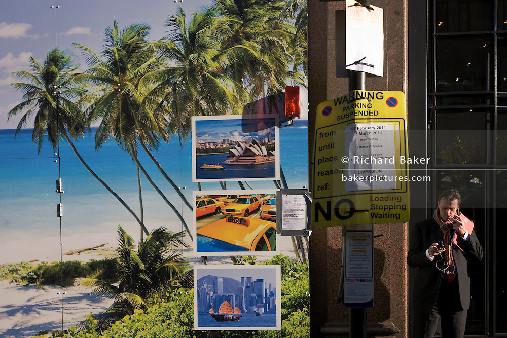 Man adjusts mp3 player with construction site showing tropical beach paradise and images of world cities with a No Parking sign