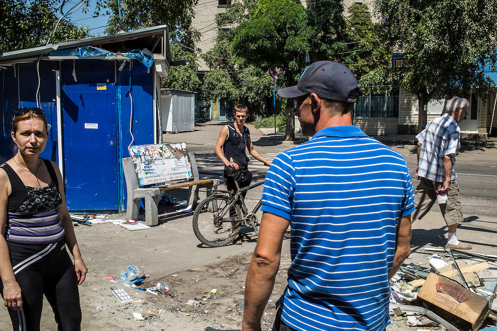 People walk around damage from the shelling of shops in the Oktyabrskaya neighborhood on Sunday, July 27, 2014 in Donetsk, Ukraine.