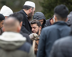 © Licensed to London News Pictures . 03/03/2016 . Manchester , UK . Shahzaib's father JAVID HUSSAIN leans on another man as Shahzaib Hussain is buried at Ashton Hurst Cemetary . Shahzaib was killed by a hit and run driver outside the mosque , on Monday 29th February 2016 . Photo credit : Joel Goodman/LNP