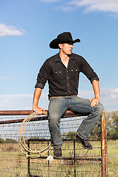 All American Cowboy sitting on a fence
