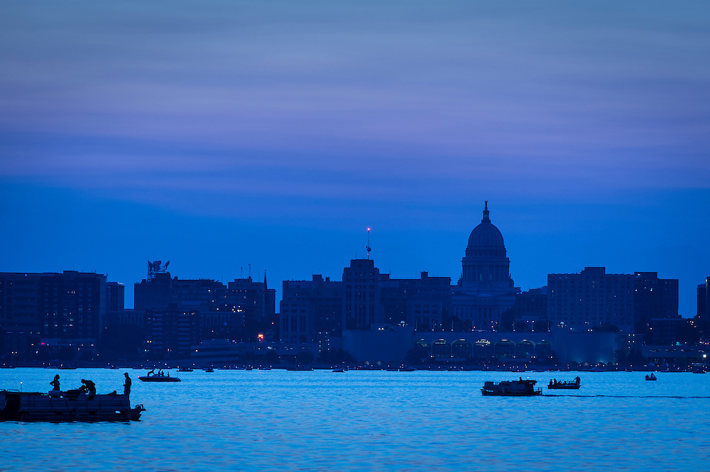 Boats gathering for Shake the Lake fireworks dot Lake Monona as sunset falls to nighttime over the downtown Madison, Wis., skyline on June 27, 2015. (Photo by Jeff Miller - www.jeffmillerphotography.com)