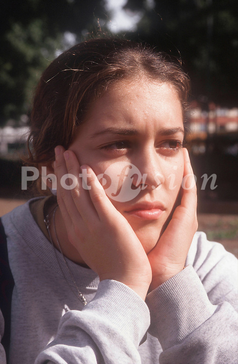 Portrait of teenage girl looking unhappy,