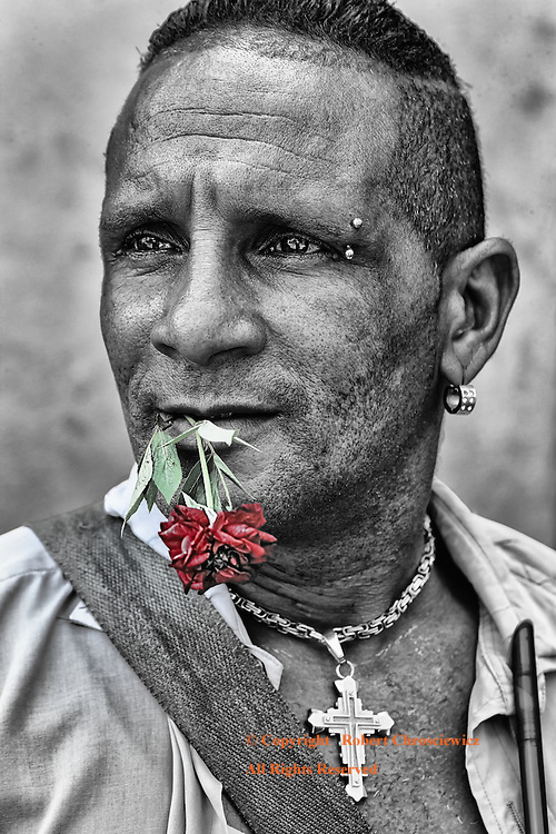 Pose with a Rose (B&W&C): A man poses for a portrait, graced with jewellery, holding a rose between his teeth, Trinidad Cuba.