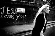 Woman crossing road. Jesus Loves You graffiti. Prostitute King's Cross London 1992.
